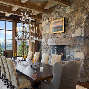 Inspiration for a rustic dark wood floor dining room remodel in Other with a standard fireplace and a stone fireplace