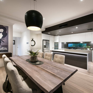 This is an example of a large contemporary open plan dining in Perth with white walls and light hardwood floors.