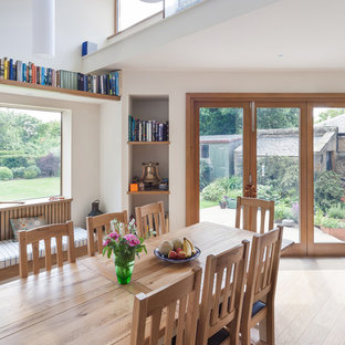 Inspiration for a small contemporary enclosed dining room in Edinburgh with white walls, light hardwood flooring and no fireplace.