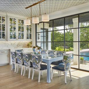 Ispirazione per una grande sala da pranzo aperta verso la cucina chic con parquet chiaro, pareti bianche, pavimento beige e soffitto in carta da parati