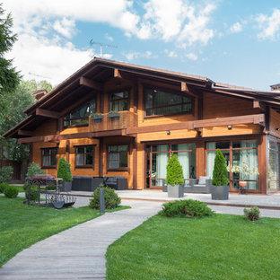 Пример оригинального дизайна: двухэтажный, деревянный, коричневый частный загородный дом в стиле рустика с черепичной крышей и двускатной крышей