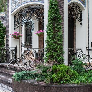 Новый формат декора квартиры: большой, двухэтажный фасад дома белого цвета в современном стиле с облицовкой из камня