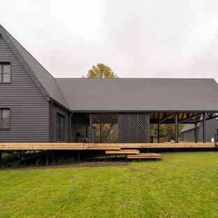 Стильный дизайн: двухэтажный, серый частный загородный дом в стиле кантри с двускатной крышей - последний тренд