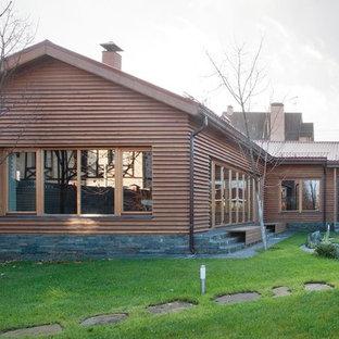 Выдающиеся фото от архитекторов и дизайнеров интерьера: одноэтажный фасад частного дома бежевого цвета в стиле кантри с облицовкой из дерева, двускатной крышей и черепичной крышей