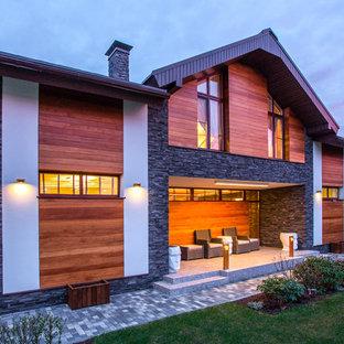 На фото: двухэтажные фасады частных домов в стиле современная классика с двускатной крышей и комбинированной облицовкой