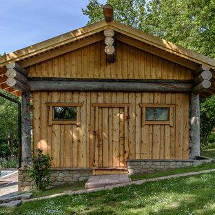 Удачное сочетание для дизайна помещения: одноэтажный фасад дома коричневого цвета в стиле рустика с облицовкой из дерева и двускатной крышей - самое интересное для вас