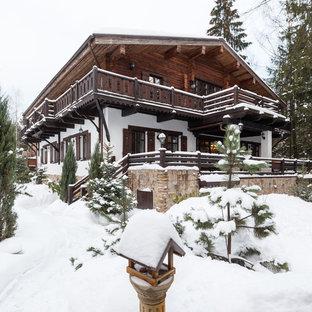 Стильный дизайн: двухэтажный частный загородный дом в стиле рустика с двускатной крышей - последний тренд