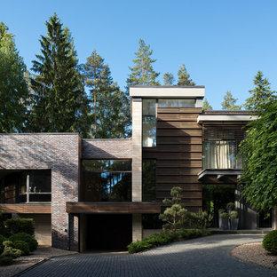 Свежая идея для дизайна: кирпичный частный загородный дом в современном стиле с плоской крышей - отличное фото интерьера
