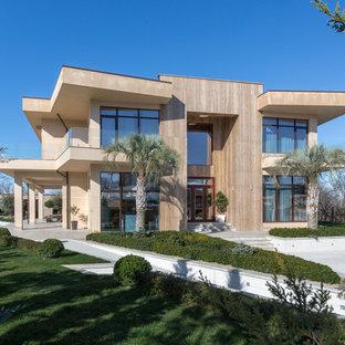 Стильный дизайн: двухэтажный, бежевый частный загородный дом в современном стиле с облицовкой из камня и плоской крышей - последний тренд
