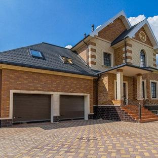 Пример оригинального дизайна интерьера: двухэтажный фасад частного дома коричневого цвета в классическом стиле с облицовкой из кирпича и двускатной крышей