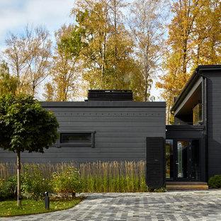 На фото: двухэтажный, черный частный загородный дом в современном стиле с