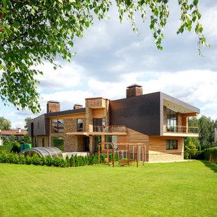 На фото: двухэтажный, разноцветный частный загородный дом в современном стиле с комбинированной облицовкой и односкатной крышей