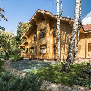 Выдающиеся фото от архитекторов и дизайнеров интерьера: двухэтажный фасад дома среднего размера коричневого цвета в стиле кантри с облицовкой из дерева и двускатной крышей