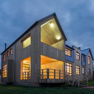 Diseño de fachada de casa marrón, campestre, grande, de dos plantas, con revestimiento de madera, tejado a doble faldón y tejado de metal