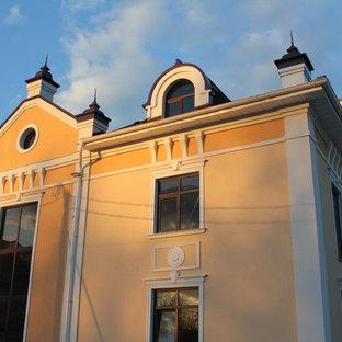 Modelo de fachada de casa pareada beige, clásica, grande, a niveles, con revestimiento de estuco, tejado a la holandesa y tejado de teja de madera