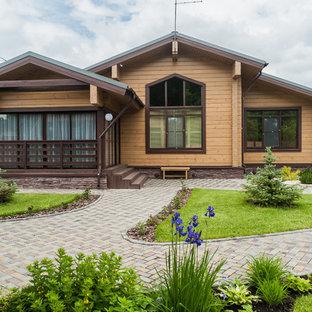 Стильный дизайн: деревянный, коричневый, одноэтажный частный загородный дом среднего размера в стиле кантри с двускатной крышей и крышей из гибкой черепицы - последний тренд