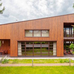 На фото: двухэтажные фасады частных домов коричневого цвета в современном стиле с облицовкой из дерева и односкатной крышей