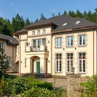 На фото: бежевый, трехэтажный частный загородный дом в стиле современная классика с облицовкой из цементной штукатурки, вальмовой крышей и металлической крышей с