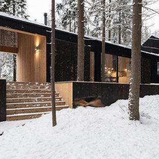 Imagen de fachada de casa negra, actual, de tamaño medio, de una planta, con revestimiento de madera, tejado de un solo tendido y tejado de metal