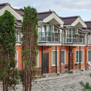 Новый формат декора квартиры: двухэтажный фасад таунхауса среднего размера коричневого цвета в современном стиле с облицовкой из кирпича и двускатной крышей