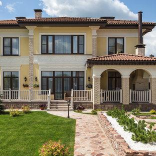 Создайте стильный интерьер: двухэтажный фасад частного дома желтого цвета в средиземноморском стиле с вальмовой крышей и черепичной крышей - последний тренд