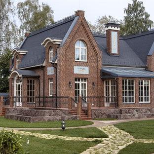 На фото: двухэтажный, кирпичный, коричневый частный загородный дом в классическом стиле с двускатной крышей с
