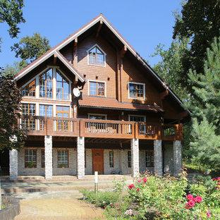 На фото: большой, трехэтажный, деревянный, коричневый частный загородный дом в стиле рустика с двускатной крышей и черепичной крышей с
