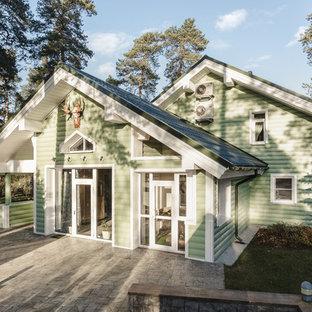 Стильный дизайн: двухэтажный, деревянный, зеленый частный загородный дом в классическом стиле с двускатной крышей - последний тренд