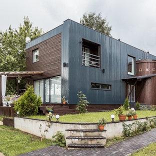 На фото: двухэтажные фасады частных домов в стиле лофт с комбинированной облицовкой и плоской крышей