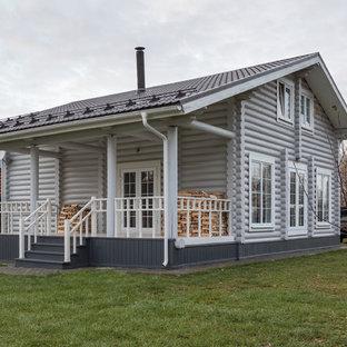 Пример оригинального дизайна: двухэтажный, деревянный, серый частный загородный дом среднего размера в стиле кантри с двускатной крышей и металлической крышей