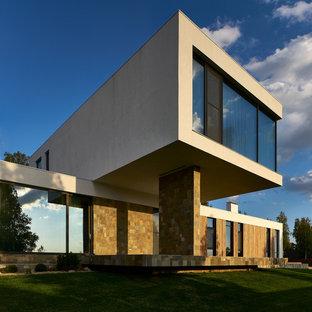 На фото: двухэтажный, бежевый частный загородный дом среднего размера в современном стиле с облицовкой из цементной штукатурки и плоской крышей с