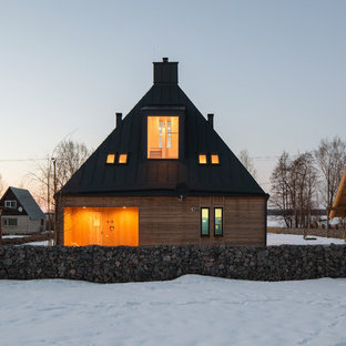 Mid-sized mountain style yellow three-story wood house exterior photo in Saint Petersburg with a gambrel roof and a metal roof