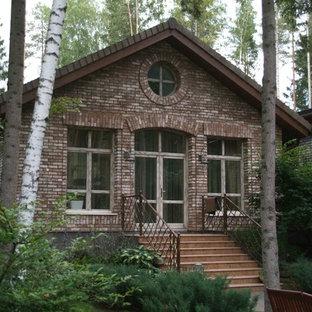 На фото: большой, кирпичный, коричневый, одноэтажный частный загородный дом в классическом стиле с двускатной крышей и черепичной крышей с