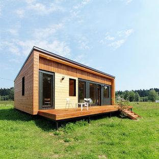На фото: маленький, одноэтажный, деревянный, коричневый частный загородный дом в скандинавском стиле с односкатной крышей и металлической крышей с