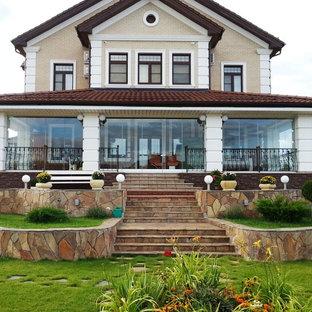 На фото: двухэтажный, бежевый частный загородный дом в стиле современная классика с двускатной крышей