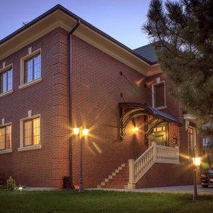 Foto de fachada de casa roja, tradicional, de tamaño medio, de dos plantas, con revestimiento de ladrillo, tejado a doble faldón y tejado de teja de madera