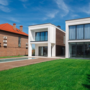 На фото: двухэтажный, разноцветный частный загородный дом в современном стиле с плоской крышей и комбинированной облицовкой