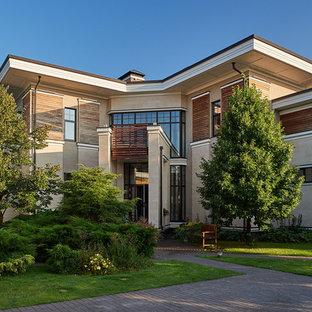 Выдающиеся фото от архитекторов и дизайнеров интерьера: фасад частного дома бежевого цвета в современном стиле