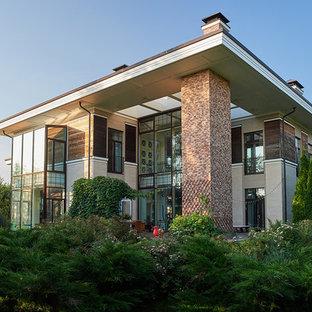 На фото: бежевый частный загородный дом в современном стиле с