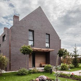 На фото: двухэтажный, кирпичный, коричневый частный загородный дом в современном стиле с двускатной крышей с