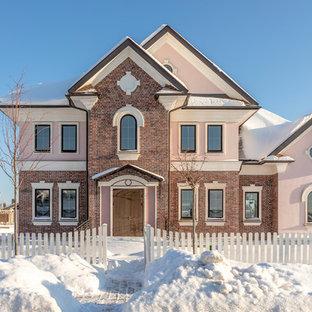На фото: трехэтажный, кирпичный, розовый частный загородный дом в стиле современная классика с двускатной крышей с