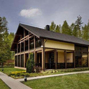 Пример оригинального дизайна: коричневый частный загородный дом в стиле рустика с двускатной крышей