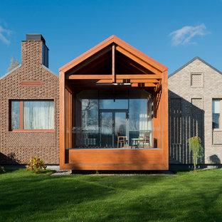 Стильный дизайн: одноэтажный, кирпичный, разноцветный дом среднего размера в современном стиле с двускатной крышей - последний тренд