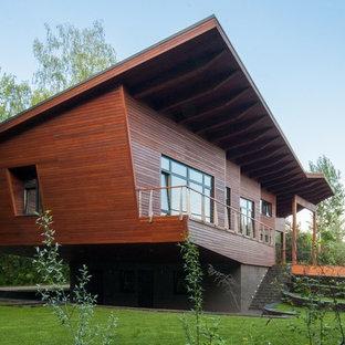 Выдающиеся фото от архитекторов и дизайнеров интерьера: большой, двухэтажный фасад дома коричневого цвета в современном стиле с облицовкой из дерева и односкатной крышей