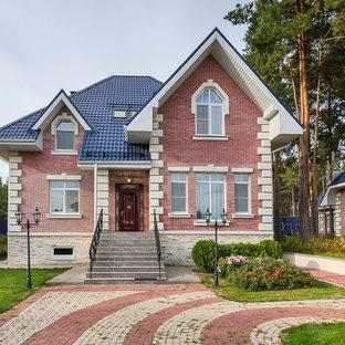 На фото: двухэтажный, кирпичный, красный частный загородный дом в классическом стиле с