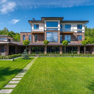 Создайте стильный интерьер: трехэтажный фасад частного дома коричневого цвета в современном стиле с облицовкой из кирпича и плоской крышей - последний тренд