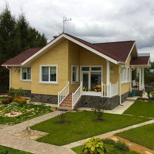 Свежая идея для дизайна: маленький, одноэтажный фасад дома желтого цвета в современном стиле с облицовкой из кирпича и двускатной крышей - отличное фото интерьера