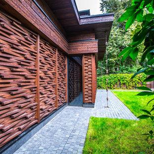 Foto de fachada marrón, escandinava, con revestimiento de madera