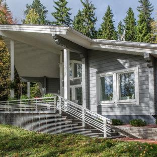Выдающиеся фото от архитекторов и дизайнеров интерьера: одноэтажный фасад частного дома серого цвета в современном стиле с облицовкой из дерева и односкатной крышей