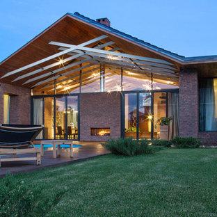 他の地域のコンテンポラリースタイルのおしゃれな家の外観 (レンガサイディング、茶色い外壁) の写真
